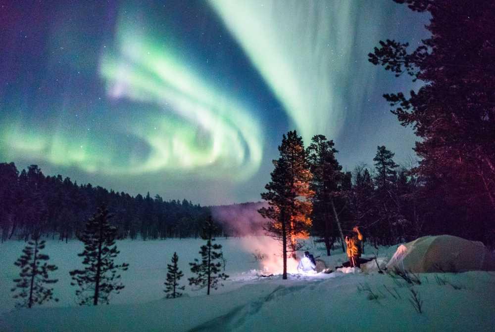 Bivouac dans la neige sous les aurores boréales en Laponie