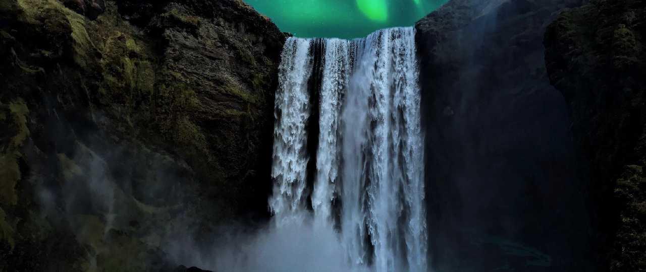 Cascade Skogafoss sous les aurores boréales