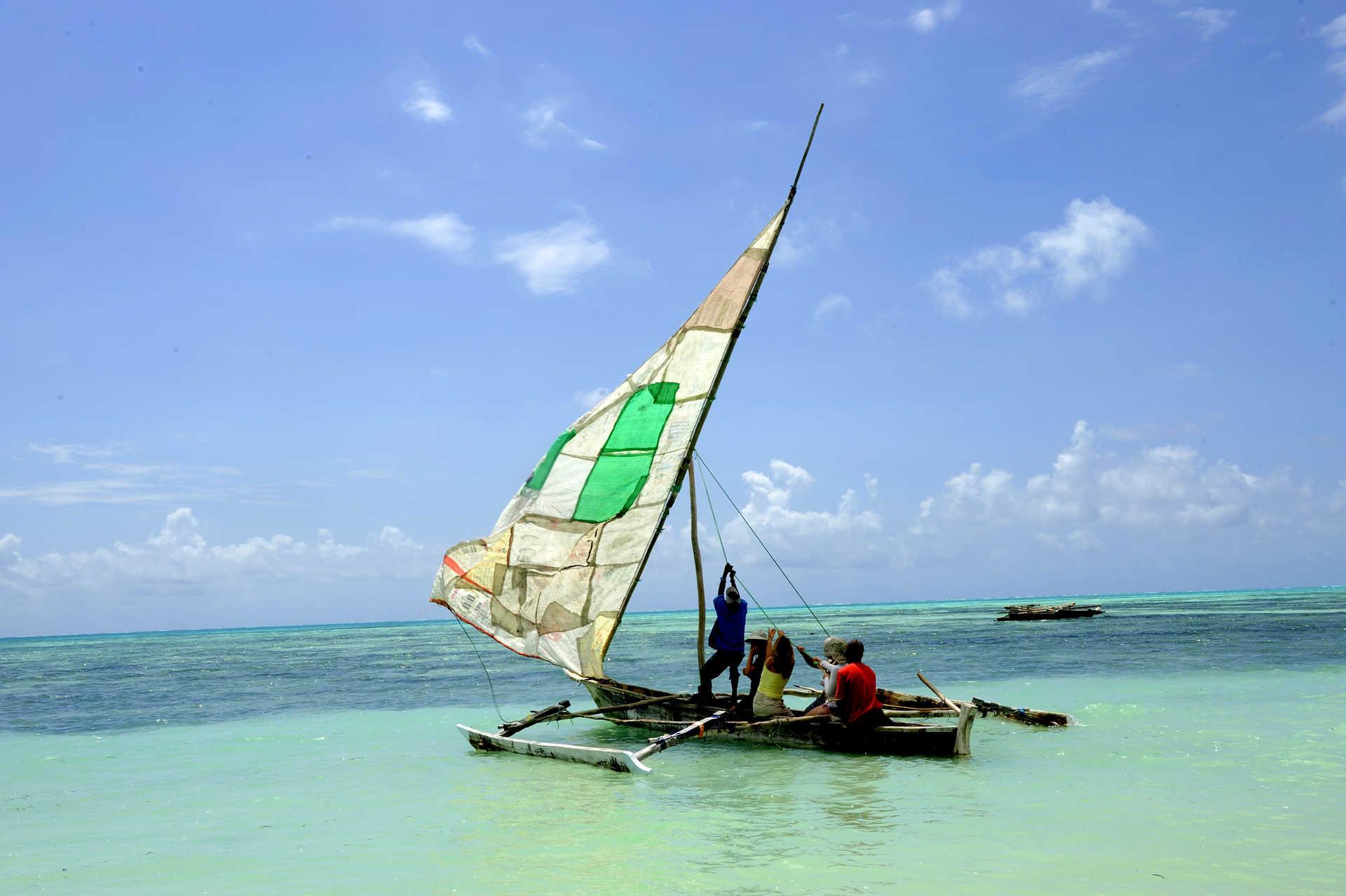 Voyageurs et locaux hissent la voile du boutre à Zanzibar