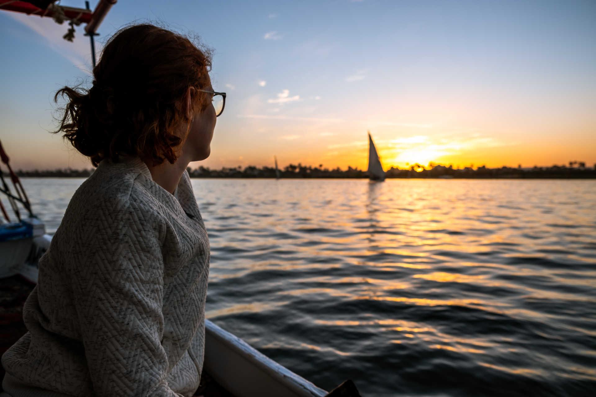 Voyageuse regardant le coucher de soleil sur le Nil