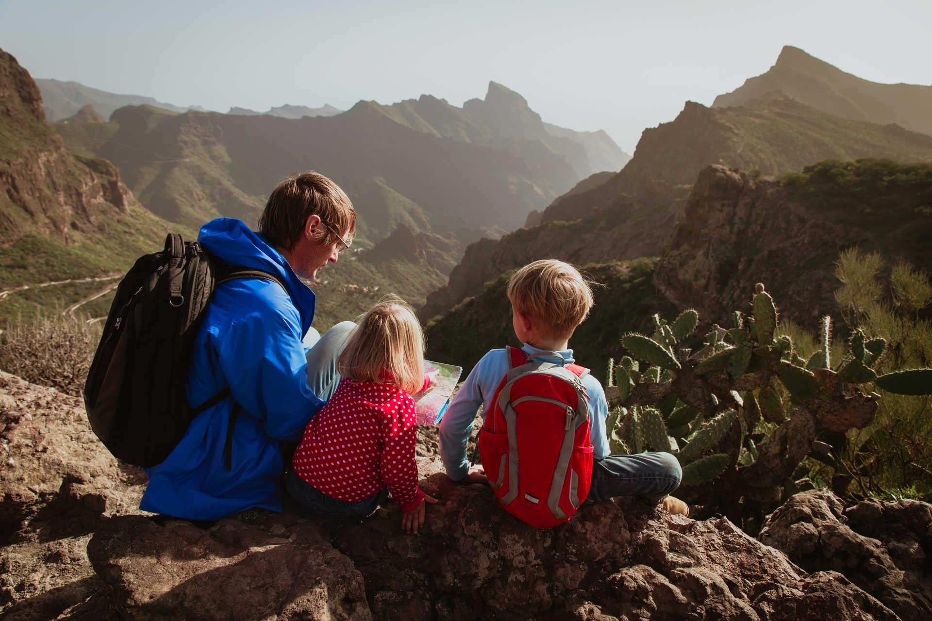 Père et ses enfants en haut d'une montagne regardant une carte