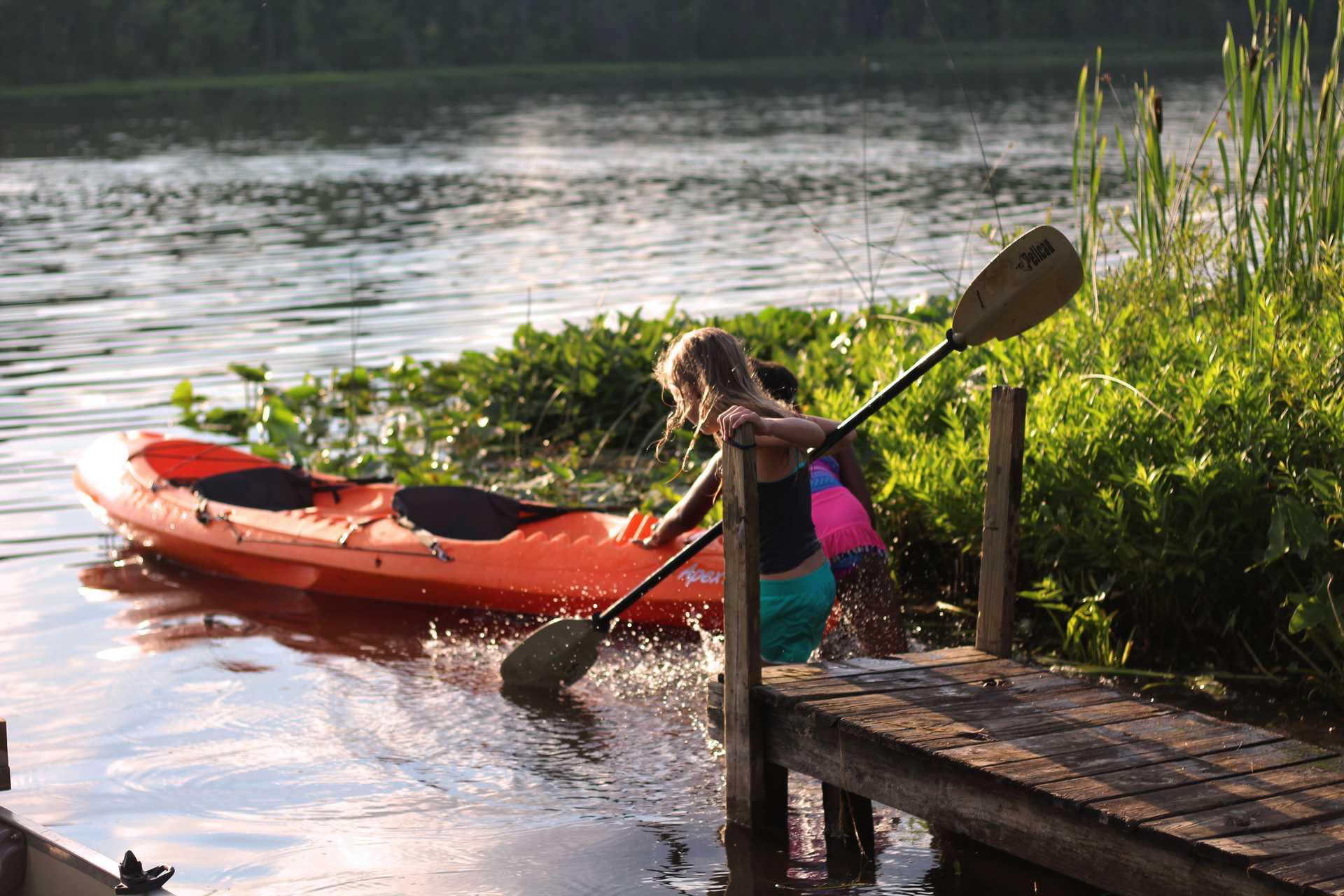 Enfant en bord de lac avec un kayak