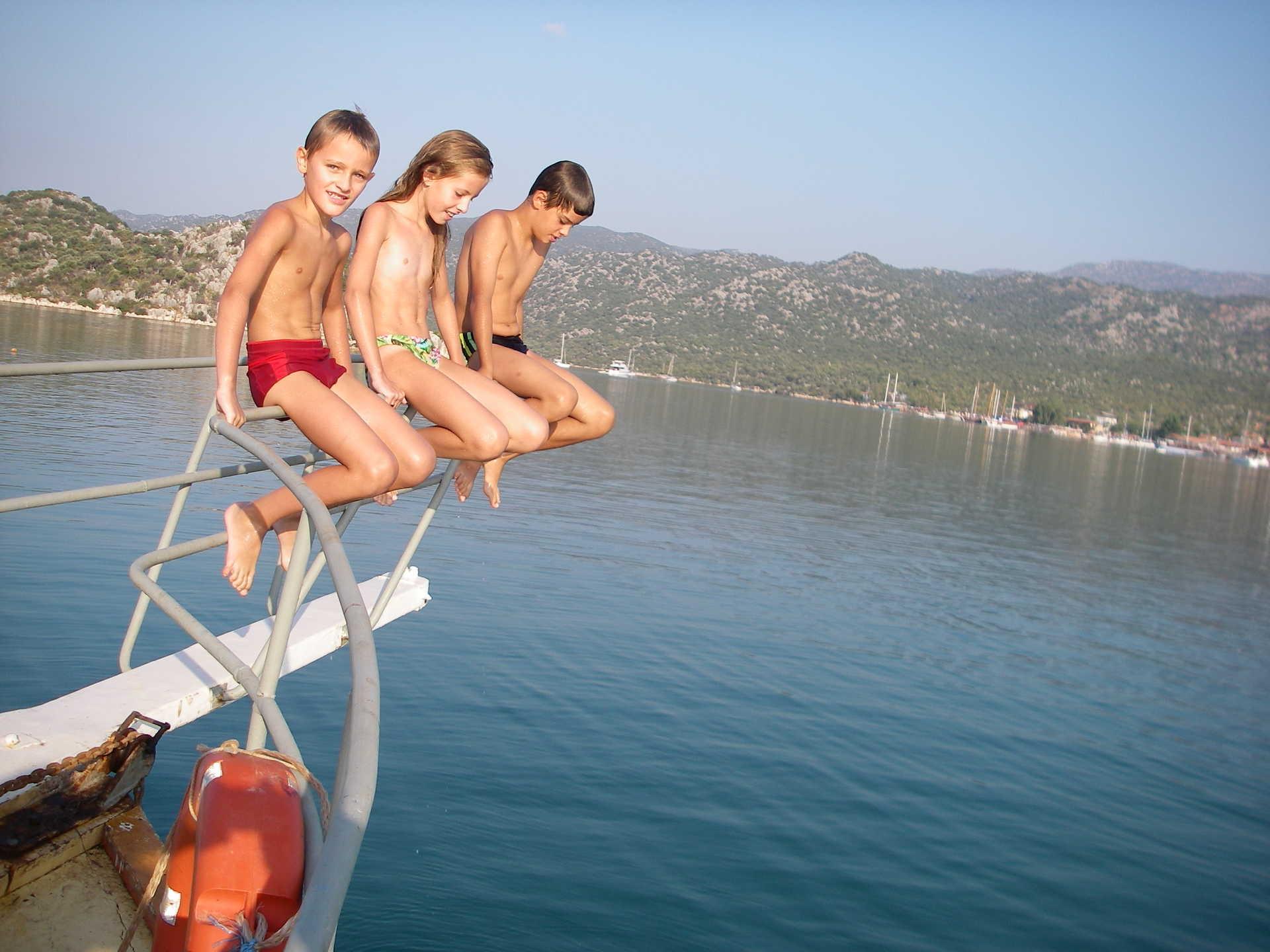 Enfants assis sur le pont avant d'un bateau au milieu de la mer