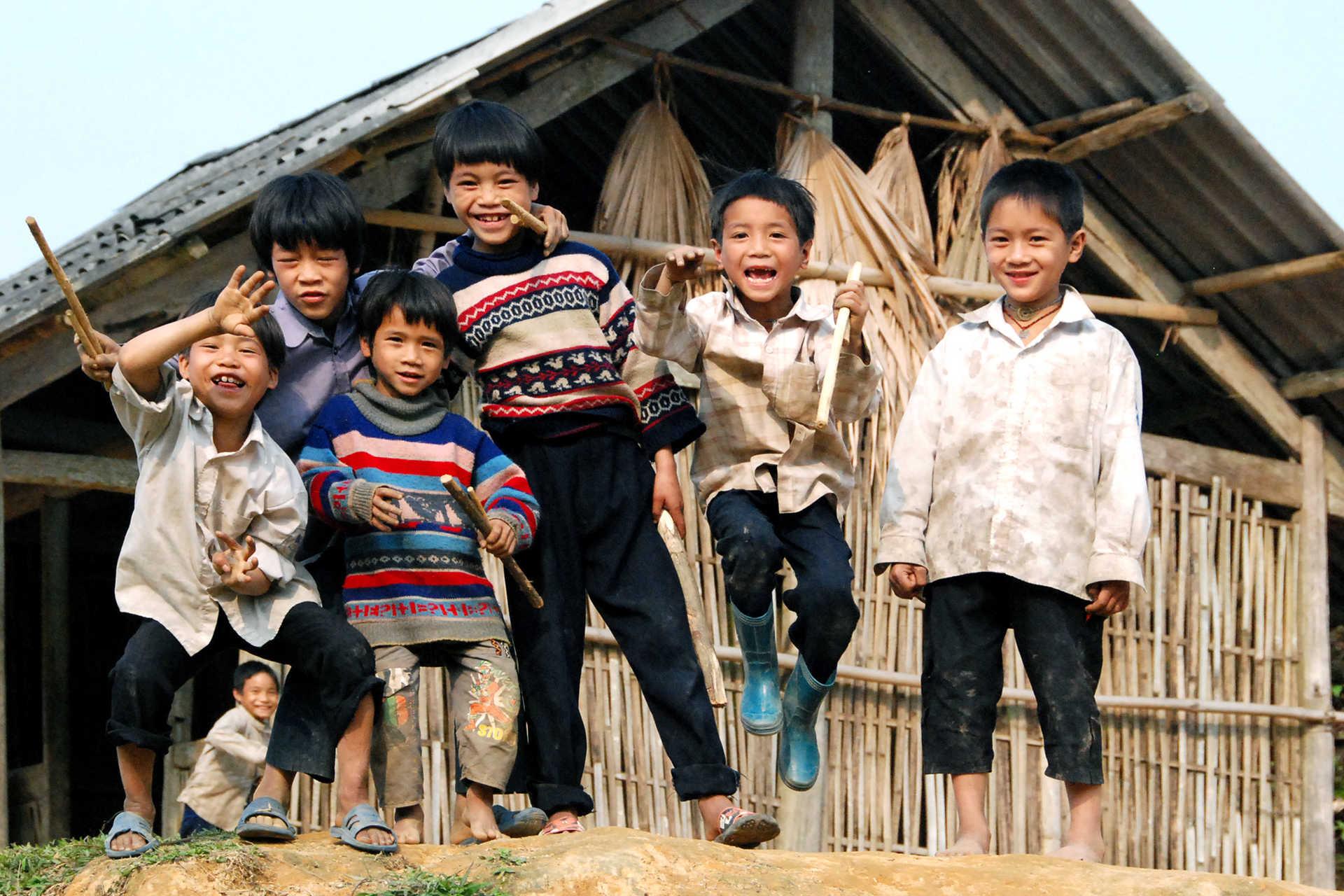 Groupe d'enfants jouant devant une maison traditionnelle au Vietnam