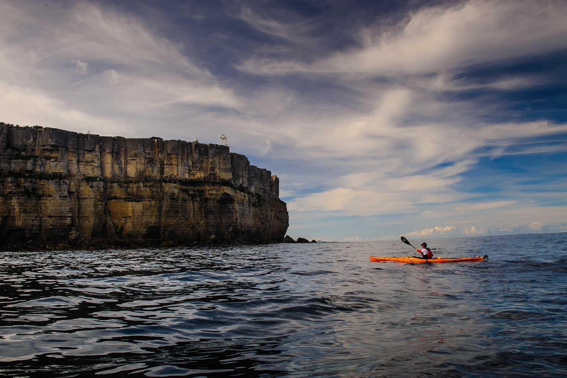 Kayakiste au milieu de l'eau et le long des falaises