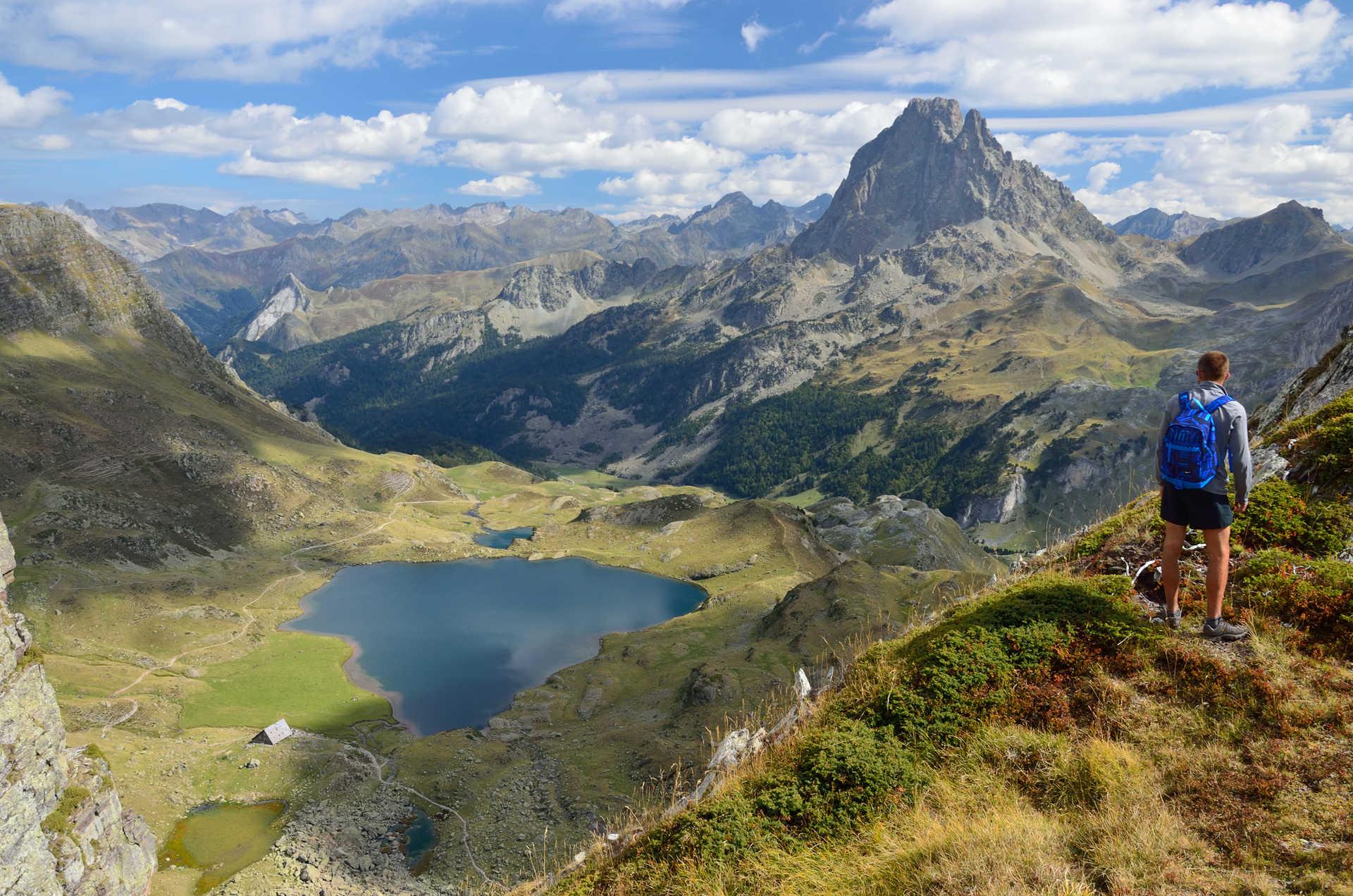 Randonneur dans les Pyrénées au dessus du lac Gentau et face au Pic du Midi d'Ossau