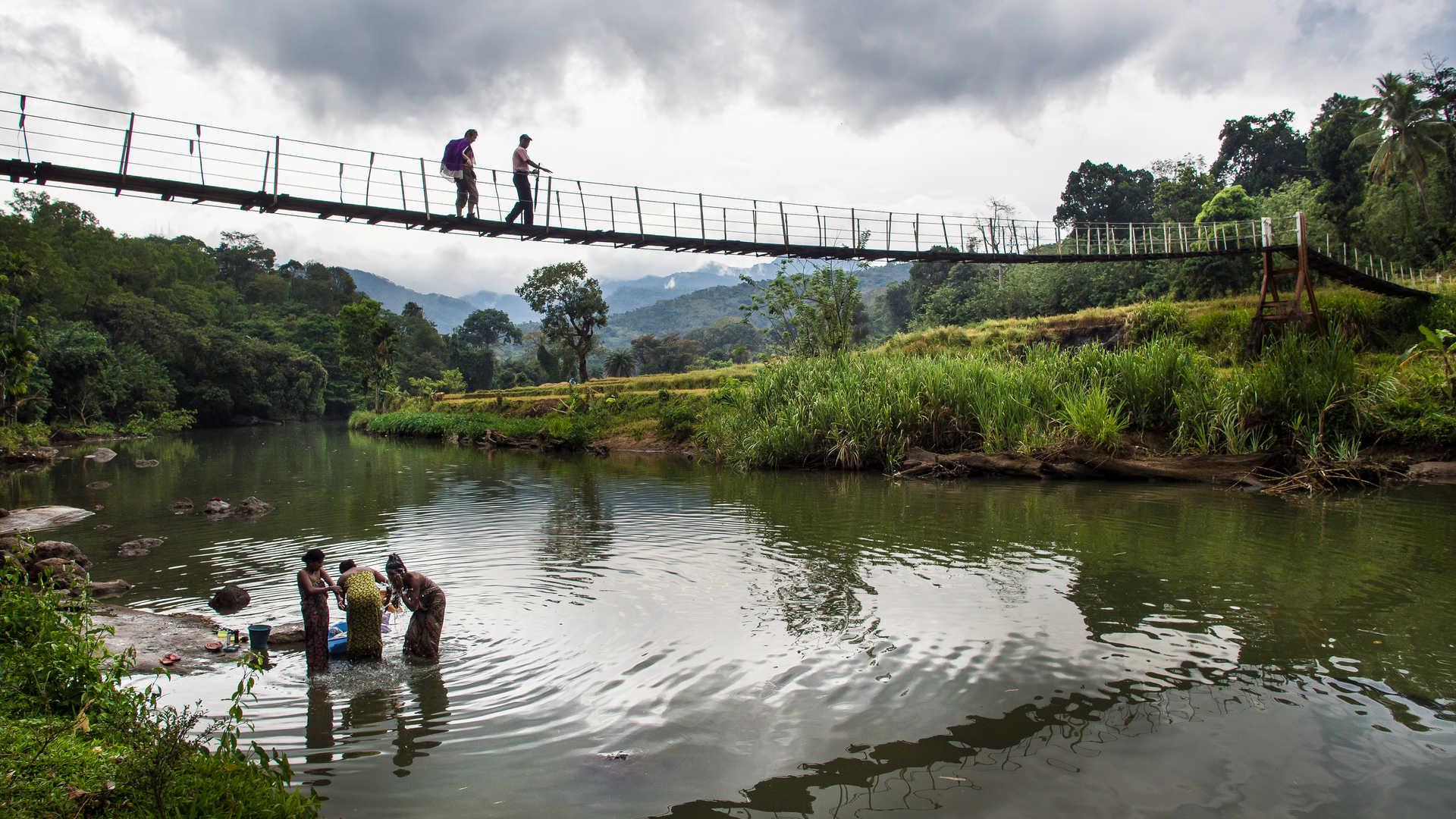 Traversée d'un pont suspendu au Sri Lanka au dessus de femmes qui se lavent