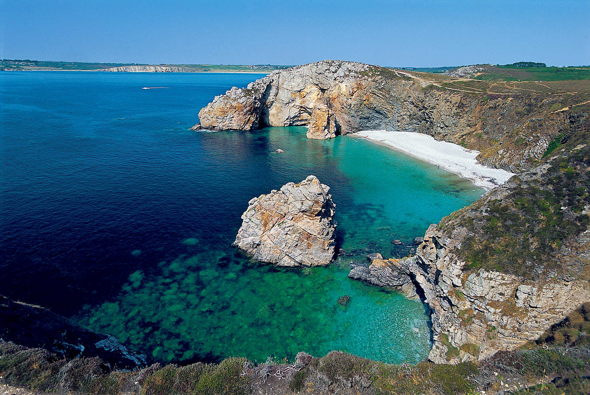 vue surplombant une plage aux eaux turquoises bordée de falaises