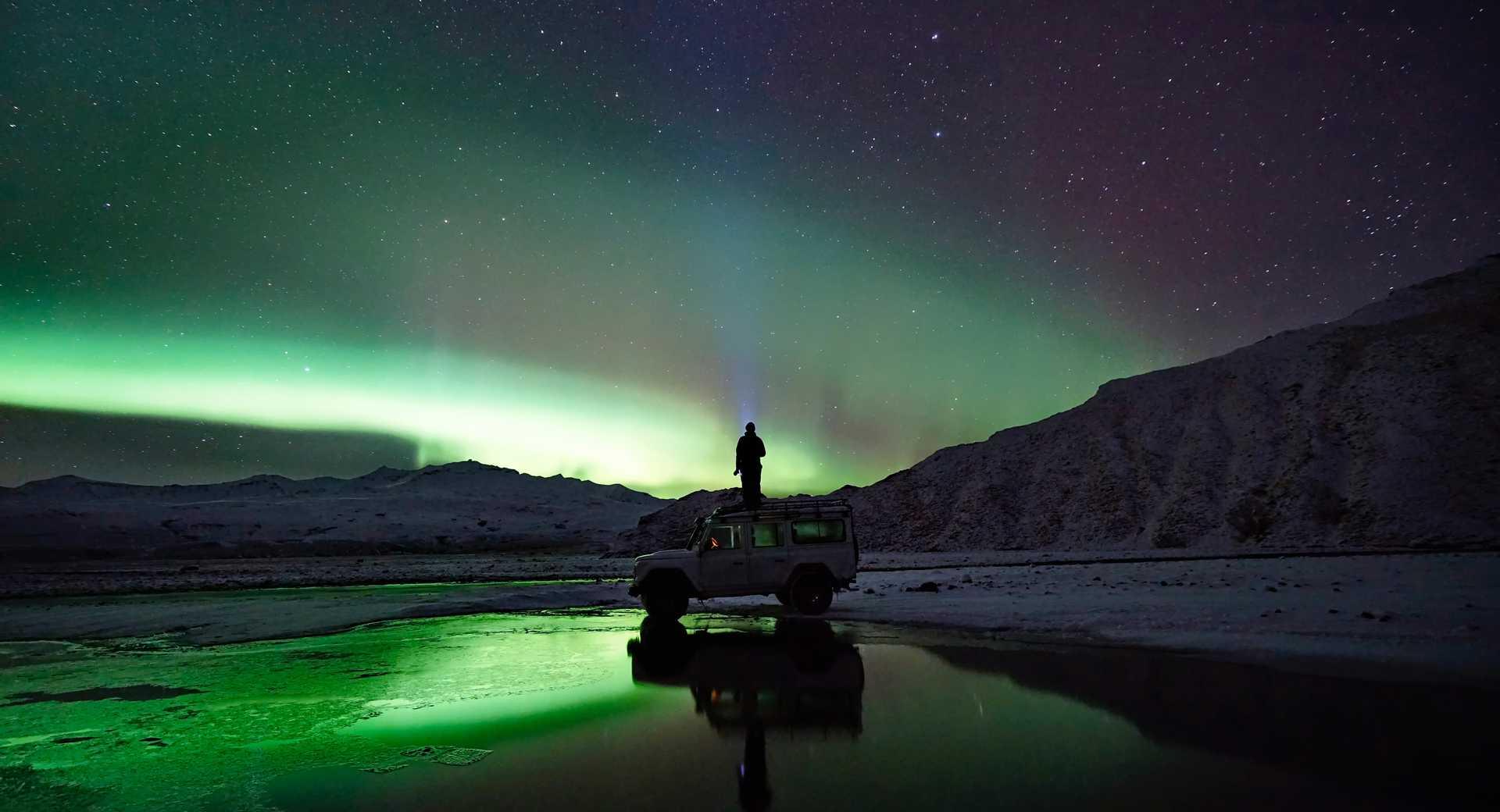 Photo d'une personne sous les aurores boréales
