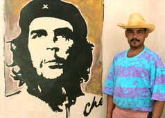 Cubain devant un portrait du Ché dans une rue de la Havane à Cuba