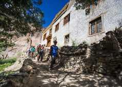Randonneurs traversant un village dans la vallée de Sumda