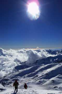 Panorama sur les sommets enneigés avec deux alpinistes