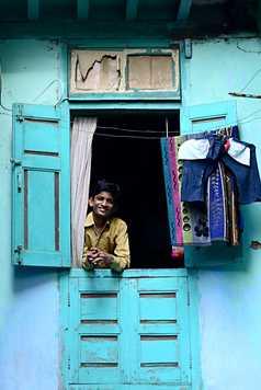 Un garçon indien regarde par la fenêtre