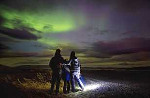 Famille admirant un aurore boréale en Islande