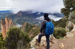 randonneur qui admire le panorama sous ses pieds, en dessous apparaissent des pics rocheux cachés par quelques nuages