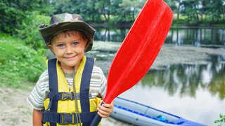 Enfant et sa pagaie près d'une rivière
