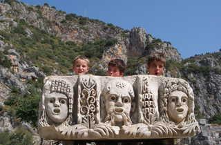 Enfants se cachant derrière un morceau de pierre sculptée