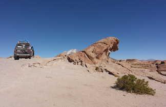 4x4 à côté d'une roche en forme de vague dans le sud lipez