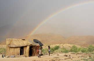 Arc-en-ciel dans un village himba en Namibie