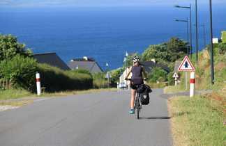 cycliste roulant sur une route avec la mer en fond