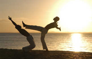 Deux jeunes-hommes faisant de la capoeira sur la plage au Brésil