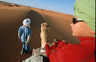 Enfant sur son chameau, face au désert, Maroc