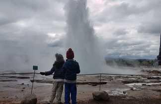 Enfants devant un geyser en Islande