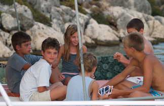 Enfants jouant aux cartes sur le pont d'un bateau