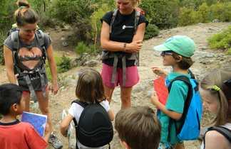 Guide  souriant à un groupe d'enfant sur un chemin de randonnée