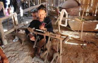 Laotienne filant la laine avec son bébé dans le dos