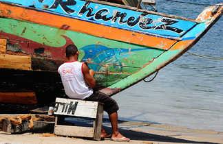 Pêcheurs en train de réparer son bateau sur une plage au Brésil