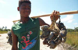 Pêcheurs tenant des crabes sur une plage au Brésil
