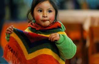 petite fille tenant son poncho multi-couleurs dans les mains