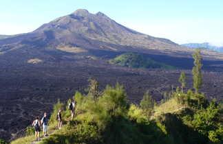 Randonnée à travers les champ de lave noire sur le flanc du volcan Batur
