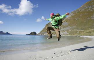 Randonneur sautant sur la plage de haukland stranda aux iles Lofoten en Norvège