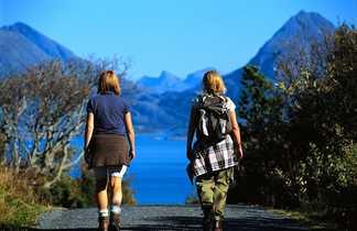 Randonneuses de dos marchant sur un chemin en Norvège au milieu des fjords