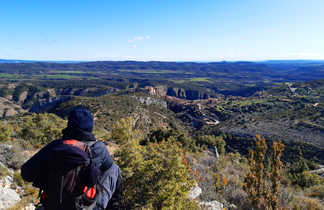 Randonneur assis qui admire la vue sur le village d'Alquezar et ces alentours