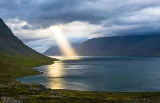 Vue panoramique sur un lac avec le soleil perçant les nuages, Irlande