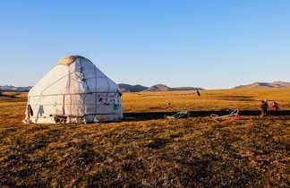 Vue sur une yourte dans un champs au coucher du soleil en Kirghizie