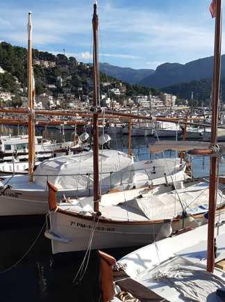 Port avec petites embarcations typiques derrière le village et les montagne de la Tramuntana