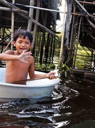 Enfant Cambodgien se baignant dans un lac proche d'un village sur pilotis