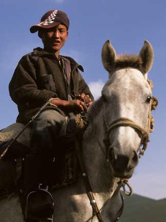 Gros plan d'un jeune cavalier sur son cheval en Kirghizie