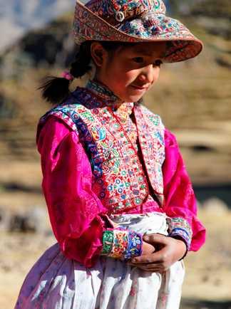 Jeune fille en habit local regardant au loin, les mains croisées