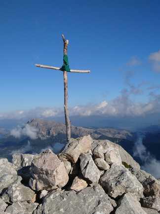 Croix en bois au sommet d'un montagne avec vue sur la mer et les montagnes au loin