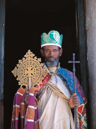 Prêtre éthiopien tenant les croix sacrées devant une église