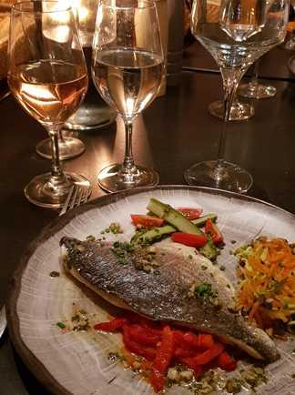 assiette avec poisson et vin blanc sur une table éclairée à l'aide d'une bougie