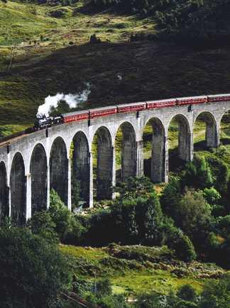 Train passant sur le viaduc  de Glenfinnan en Ecosse