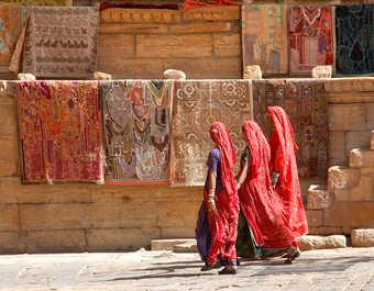Trois indiennes en sari marchants devant un mur coloré, Rajasthan