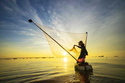Pêcheur indonésien  jetant son filet au coucher du soleil
