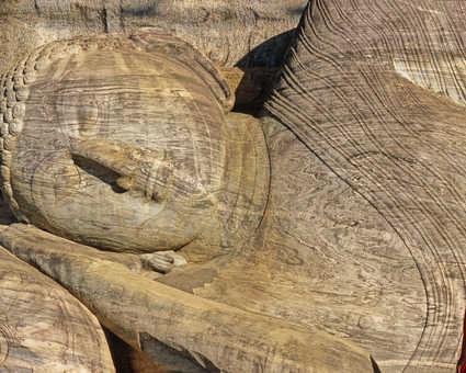 Moine-bouddhiste-devant-une-statue-de-bouddha-à-Polonnarwa